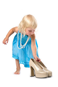 funny little blonde girl in blue dress and pearl necklace with pair of big high-heeled shoes in hand, isolated on white
