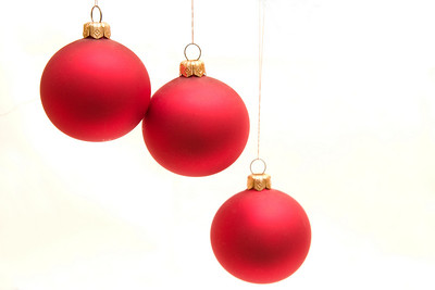 three red Christmas bulbs isolated on white