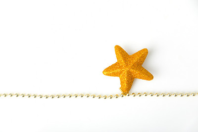 Gold star with chain as christmas decoration on white background