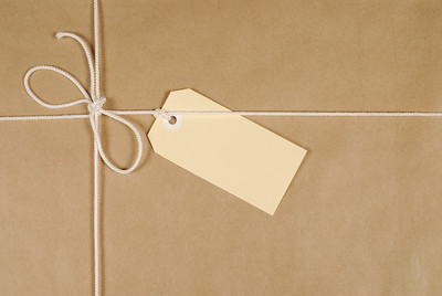 Parcel wrapped in mottled brown paper with cream cotton string and buff address label.
