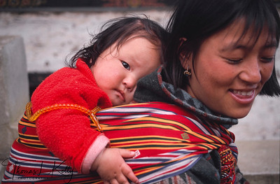 Bhutanese mother uses her traditional kira to carry her child. Women wear an ankle-length dress, the kira, which is clipped at one shoulder and tied at the waist. An accompaniment to the kira is a long-sleeved blouse, the toego, which is worn underneath the outer layer.