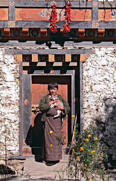 Chilies drying over a house entrance way with a Bhutanese woman sunning herself with her cat in hand.