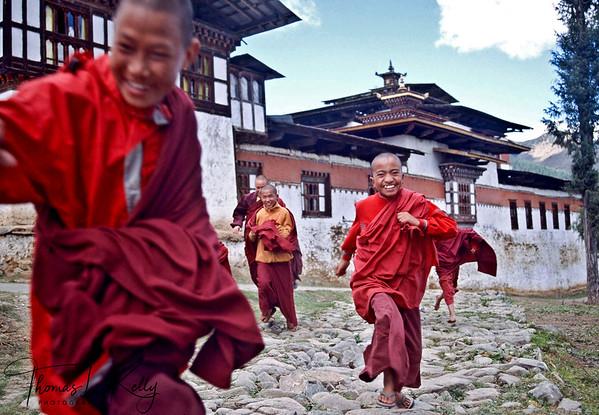 Young monks running out of Gangtey Monastery. Phobjika, Bhutan.