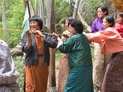 Women help to pull up a prayer flag in Tang Valley. Bhutan.