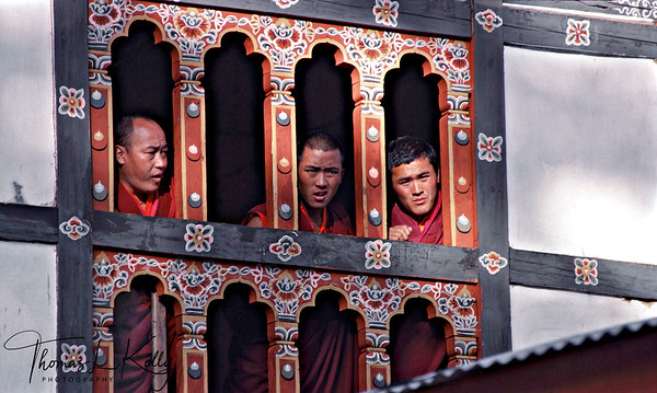 Bhutan has forged a way of life centered on Buddhist principles, reverence for nature, cultural heritage, good governance, and an attachment to traditional garb and customs. Budhist monk takes in the mid-day sun inside the Ripung dzong.  Paro, Bhutan.