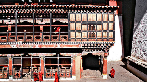 Bhutan has forged a way of life centered on Buddhist principles, reverence for nature, cultural heritage, good governance, and an attachment to traditional garb and customs. Budhist monk takes in the mid-day sun inside the Ripung dzong.  Paro, Bhutan. .