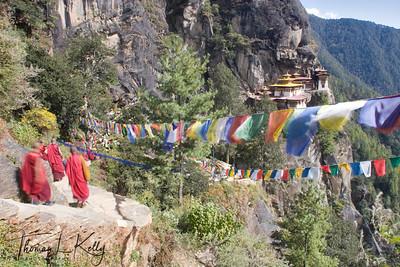 Buddhist monks walking uphill to Taktsang Monastery.  Paro Valley, Bhutan.