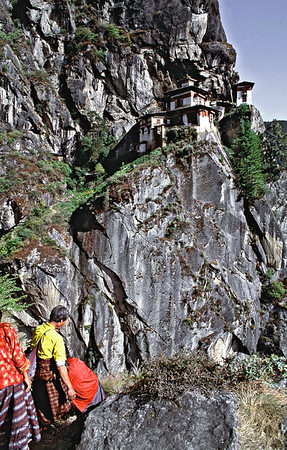 Bhutanese pilgrims dressed in their traditional ghos visit Taktsang Monastery.  Paro Valley, Bhutan.