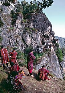 Bhutanese pilgrims dressed in their traditional ghos visit Taktsang Monastery.  Paro Valley, Bhutan.