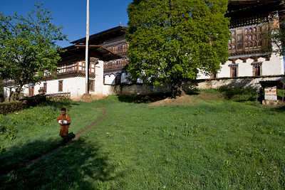 Bhutanese school boy walks aside Ugyen Choling Palace.  Bumthang. Bhutan