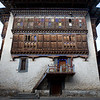 Wangde Choeling Dzong : Along the Chamkhar River in central Bhutan, Wangduechhoeling Palace rises from the Jakar valley floor, surrounded by the verdant colors of the region's rice fields.  Constructed as a private residence in 1857 for Trongsa Penlop Jigme Namgyel, a legendary Bhutanese warrior, the palace was the birthplace of the first King of Bhutan, Ugyen Wangchuck, Jigme Namgyel's son. Under King Ugyen Wangchuck, Wangduechhoeling became the seat of national power in the early twentieth century, housing the king's offices and courts. In 1950, the capital was moved to Paro, and ten years later the royal family followed.  For the last 50 years, Wangduechhoeling has been largely neglected, though a monastic school housing a community of 30 monks has occupied a small portion of the rooms since 2004.  The palace and its ancillary structures remain a classic example of nineteenth century Bhutanese architecture. White stone walls bonded with earthen mortar, wattle-and-daub partitions, and richly ornamented timber details characterize the complex, which is built around a central courtyard and houses priceless murals, texts, sculptures, and textiles.  Bumthang, Bhutan.