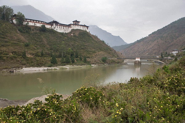 """Wangdu Phodrang is a town and capital of Wangdue Phodrang District in central Bhutan.   The town shares its name with the dzong, built in 1638 which dominates the district. The name is said to have been given by Shabdrung Ngawang Namgyal who was searching for the best location for a dzong to prevent incursions from the south. At the chosen spot the Shabdrung encountered a boy named Wangdi playing beside the river and hence named the dzong """"Wangdi's Palace"""".  Wangdue Phodrang District, Bhutan"""