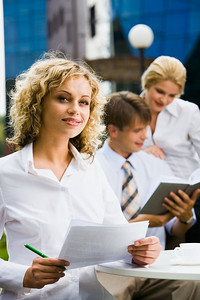 Young beautiful smiling woman is holding  paperwork and green pen on a background of two businesspeople and building