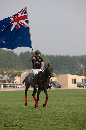New Zealand Polo Player, Simon McDonald fluttering their National flag prior to Match. National Stadium (Bird's Nest). China.