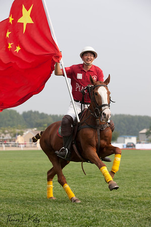 Chinese Polo Player, Xia Yang fluttering their National flag prior to Match. National Stadium (Bird's Nest). China.