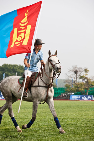 Genghis Khan Polo Club, Mongolia player flutter their National flag prior to match. National Stadium (Bird's Nest). China.