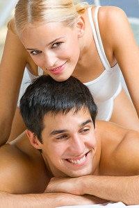 Portrait of young attractive happy amorous couple in bedroom
