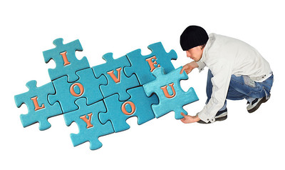 young man puts puzzle on white background