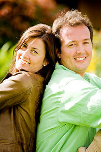 happy couple portrait outdoors smiling - back to back