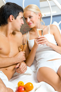 Young happy couple celebrating with champagne at bedroom