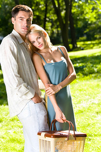 Young happy couple with picnic basket walking together outdoors
