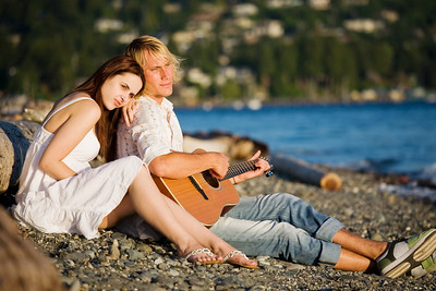 A caucasian couple sitting on the beach playing guitar