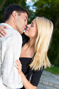 Young happy couple kissing and embracing, outdoors