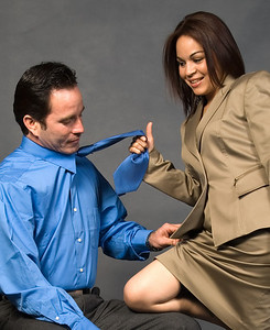 Business man sitting down with a business woman standing with a knee on his chair pulling on his tie