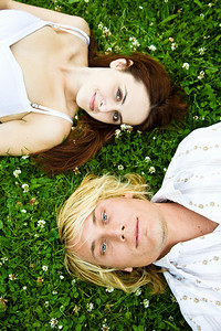 A happy young caucasian couple lying down on the grass