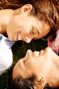 beautiful couple smiling and facing each other on the floor
