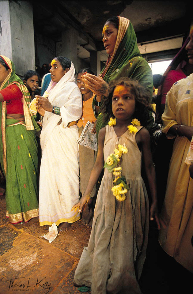 child is brought by her mother to the Yellama festival to be dedicated. Girls who<br /> enter service to the goddess are usually from landless, low-caste families who work<br /> as bonded laborers for powerful landlords. Upon reaching menarche, many girls will<br /> sell sex in rural towns to support their families; others will move to the red-light<br /> districts of the big cities. Over 50% of the working prostitutes in Mumbai are<br /> Devadasi.<br /> Karnataka, Saundatti, India.