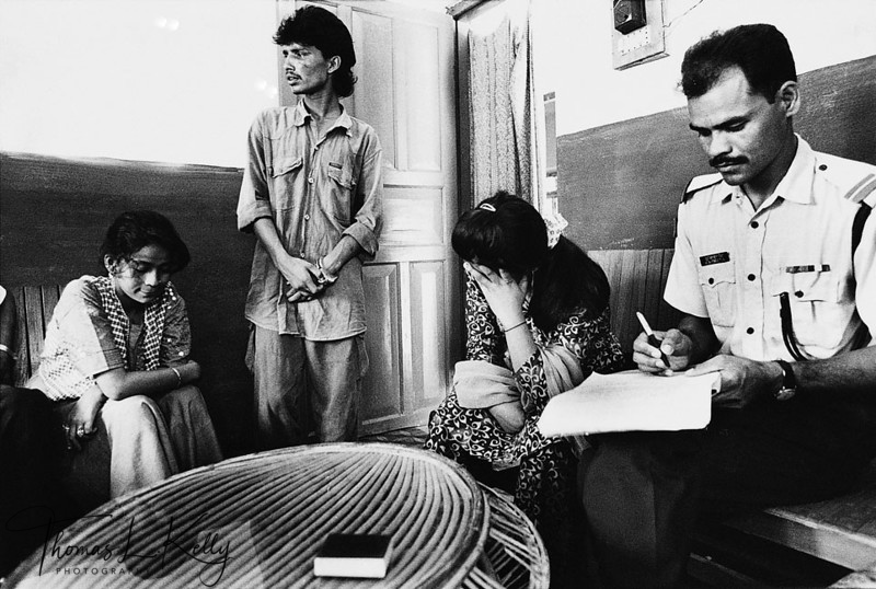 BUSTED<br /> Convicted trafficker Rajan (center) is booked on evidence from two of his Nepali<br /> victims, Jamuna (left) and Jyoti (right, all name changed). Jamuna spent three years<br /> in brothels of Mumbai, India, before being rescued in 1998. Rajan trafficked Jyoti's<br /> sister in the ealy 1990s, and later sold Jyoti to the same brothel.<br /> Hetauda jail, Central Nepal.