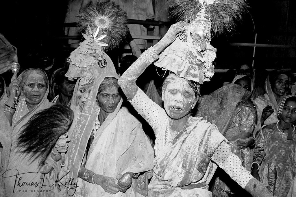 YELLAMA DEVADASI<br /> Weaving in trance, drenched in sacred healing turmeric, devadasis 'handmaidens of the Goddess' sway through the crowds, with images of goddess Yellama balanced on their heads, a renewal of the life force at her yearly festival.  Auspicious but impure, according to Medieval temple records, devadasis brought critical income to the temples. Clients made offerings for physical union with the Goddess in the form of devadasis. Today, Yellama's devotees are mostly bonded laborers who till the soil for landlords, and many devadasis find themselves in Mumbai red light districts. HIV and STD run rampant in these communities.<br /> Saundatti, Karnataka, India.
