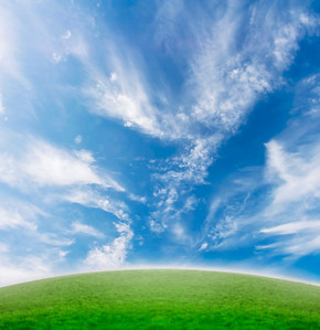 Simple beautiful nature background with green grass and blue vivid sky with clouds.
