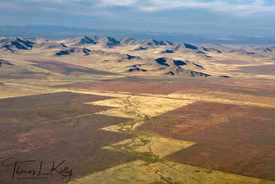 Aerial view of variation of landscape from bare lands to thinly forested area, from rivers to fresh water lakes, from solitude ger to densely populated area  and from dessicated mountains to green steppes of Mongolia, on the way to West Taiga from Ulaanbatar. Mongolia.