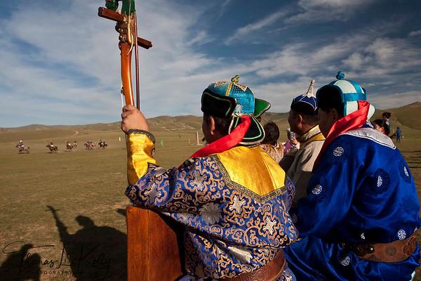Mongolian musicians watch polo match. Monkhe Tingri, Mongolia