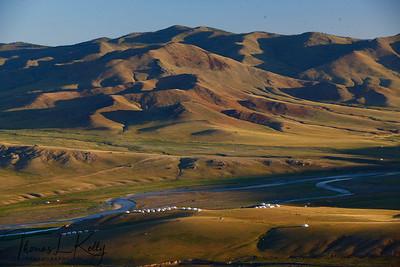 Clustered Monkhe Tingri ger camps on the vast rolling steppes alongside swirling Orkhon River. Arkhangai, Mongolia.