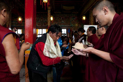 Monks, amchis (Tibetan doctors) and pilgrims receive sacred pills and khata (scarf) as blessings from Ven. Chokling rimpoche, at the conclusion of Yuthok Nyingthin Lung puja. White Monastery in Bouddha, Kathmandu, Nepal.