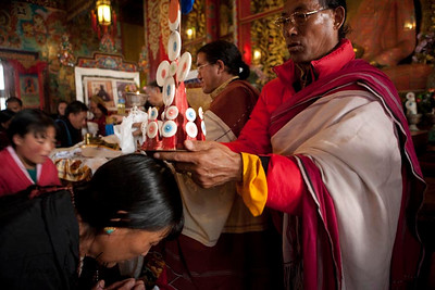 Monks, amchis (Tibetan doctors) and pilgrims receive sacred torma blessings from Ven. Chokling rimpoche, at the conclusion of Yuthok Nyingthin Lung puja. White Monastery in Bouddha, Kathmandu, Nepal.