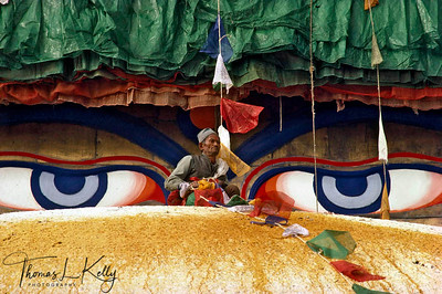 Newar man putting prayer flags around Bouddhanath stupa.  Kathmandu, Nepal.