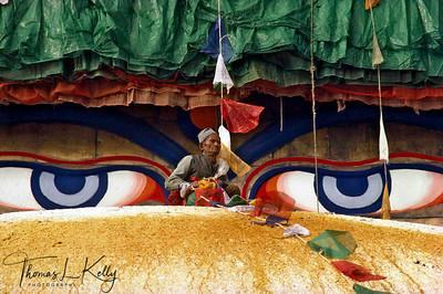 Newar man putting prayer flags around Bouddhanath stupa.  Kathmandu, Nepal.