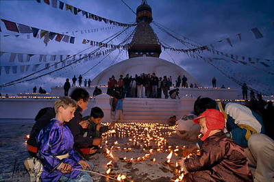 Tibetan pilgrims, monks and nuns lighting butter lamps at the base of Boudhanath Stupa during the Losar-Tibetan New Year. Kathmandu, Nepal.