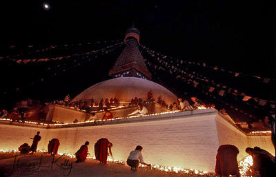Tibetan pilgrims, monks and nuns lighting butter lamps at the base of Boudhanath Stupa during the Losar-Tibetan New Year. Kathmandu, Nepal.