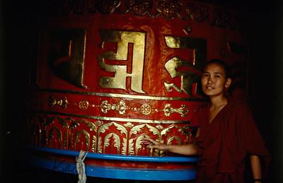 Buddhist Ani (Nun) spins Prayer Wheel sending prayers to all sentient beings.  Swayambhunath. Nepal.