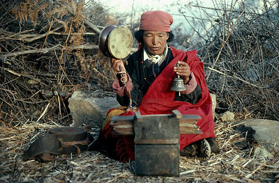 At the foot of Mount Kailash a Buddhist nun recites mantras.  She beats a stretched sheepskin drown, damaru, and rings a bell.  On her lap is a human thigh bone, Kagling.  Pictures of the Karmapa rest at her feet.  She is performing a Chod ritual -- lost souls are called forth and fed spiritually.