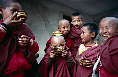 Young Tibetan nuns have yogurt in wooden bowl. Tshurpu Monastery. Tibet.