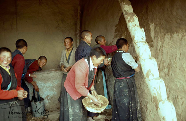 Tirdrom: Buddhist nuns work together mud-painting the walls of the hermitage. Tibet.