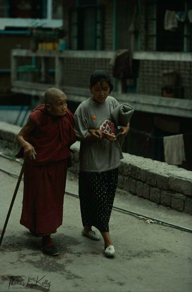 In Dharamsala an old Buddhist nun is assisted by a young relative.