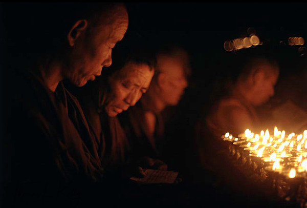 Monks and Nuns offer butter lamps at Mahabodhi Temple. Kalachakra Initiation, Bodhgaya, India.