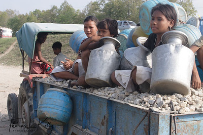 Due to born to poor parents, these kids are apparently denied to go to school and are bound to follow their parents profession of crushing gravels to suppliment the family income.  Young tharu boys and girls, hitching a ride on a tractor which is taking a crushed gravel, to fetch drinking water in blue barrel. Lack of proper tap-stand service and inconvenience of living, they are bound to travel as far as 30 kms from the place they live.  Hetauda, Nepal.